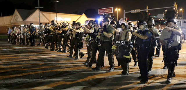 Police advance to clear people Monday, Aug. 18, 2014, during a protest for Michael Brown, who was killed by a police officer Aug. 9 in Ferguson, Mo. Brown's shooting has sparked more than a week o ...