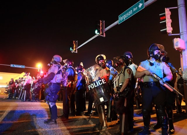 Police stand guard Monday, Aug. 18, 2014, in Ferguson, Mo. The Aug. 9 shooting of Michael Brown by a police officer has touched off rancorous protests in Ferguson, a St. Louis suburb where police  ...