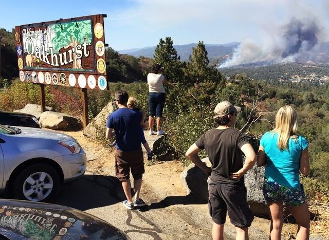 People watch a fire burning from the Highway 41 overlook on the way north into Oakhurst, Calif., Monday, Aug. 18, 2014. The fire is burning north of the community. (AP Photo/The Fresno Bee, Eric P ...