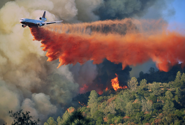 An air tanker drops fire retardent on a fire which was burning on a ridge northeast of Oakhurst, Calif., Monday, Aug. 18, 2014. One of several wildfires burning across California prompted the evac ...