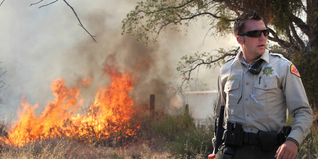 A Kern County Sheriff Deputy helps out with evacuations above Wofford Heights, Calif, Monday, Aug. 18, 2014. The fire in Wofford Heights near Lake Isabella has grown to about slightly more than 1  ...
