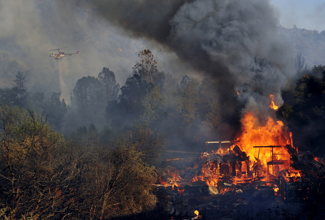 A structure burns along Highway 41 in Oakhurst, Calif., Monday, Aug. 18, 2014. One of several wildfires burning across California prompted the evacuation of hundreds of people in a central Califor ...
