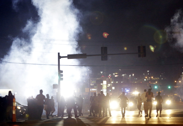 Protesters walk through a cloud of tear gas Monday, Aug. 18, 2014, in Ferguson, Mo. The Aug. 9 shooting of Michael Brown by police has touched off rancorous protests in Ferguson, a St. Louis subur ...
