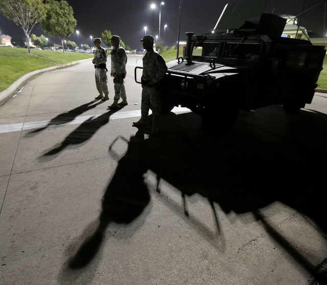 This Aug. 18, 2014 file photo shows members of the Missouri National Guard standing watch outside a command post near a protest for Michael Brown, who was killed by a police officer Aug. 9 in Ferg ...