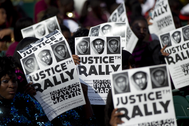 This April 1, 2012 file photo shows members of the audience holding signs of support as thousands gathered in downtown Miami demanding justice for Trayvon Martin during a rally that featured natio ...