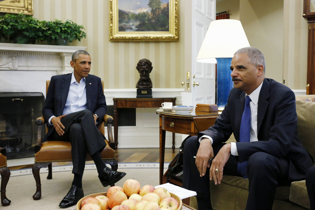 This Aug. 18, 2014 file photo shows President Barack Obama meeting with Attorney General Eric Holder  in the Oval Office of the White House in Washington. Holder, who is leading the federal respon ...