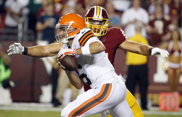 Washington Redskins outside linebacker Ryan Kerrigan sacks Cleveland Browns quarterback Brian Hoyer during the first half of an NFL preseason football game Monday, Aug. 18, 2014, in Landover, Md.  ...