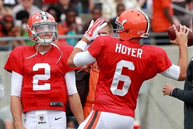 In this Aug. 2, 2014, file photo, Cleveland Browns quarterback Brian Hoyer throws a pass as Johnny Manziel looks on at NFL practice held at InfoCision Stadium in Akron, Ohio. Browns coach Mike Pet ...
