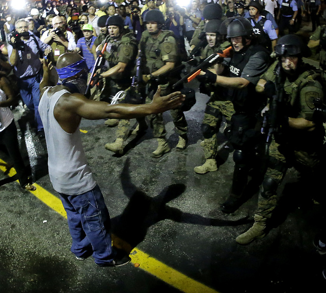 Police arrest a man as they disperse a protest in Ferguson, Mo. early Wednesday, Aug. 20, 2014. On Saturday, Aug. 9, 2014, a white police officer fatally shot Michael Brown, an unarmed black teena ...