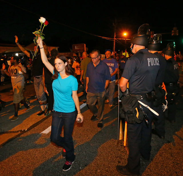 A protester holds roses in the air as she marches with others past police officers in Ferguson, Mo. on Tuesday, Aug. 19, 2014. On Saturday, Aug. 9, 2014, a white police officer fatally shot Michae ...