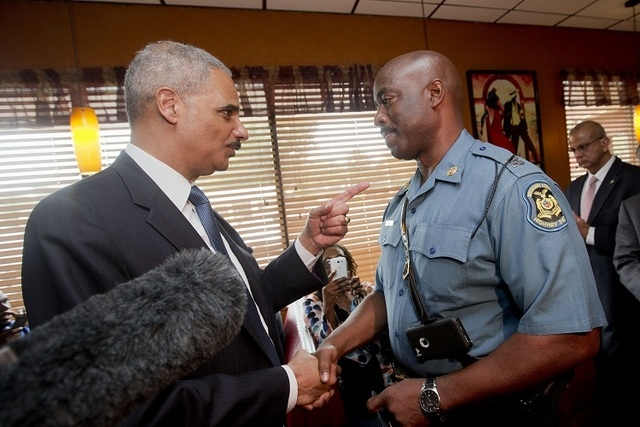 Attorney General Eric Holder talks with Capt. Ron Johnson of the Missouri State Highway Patrol at Drake's Place Restaurant, Wednesday, Aug. 20, 2014 in Florrissant, Mo. Holder arrived in Missouri  ...