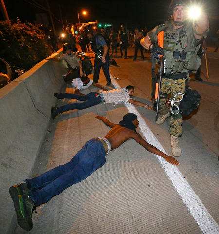 Police begin arresting dozens of protesters on West Florissant Avenue after they refused to leave the area and some began throwing objects at officers in Ferguson, Mo. early Wednesday, Aug. 20, 20 ...