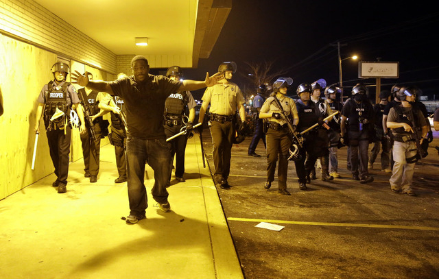 A community leader tries to get protesters to move back as police attempt to disperse a crowd in Ferguson, Mo. early Wednesday, Aug. 20, 2014. On Saturday, Aug. 9, 2014, a white police officer fat ...