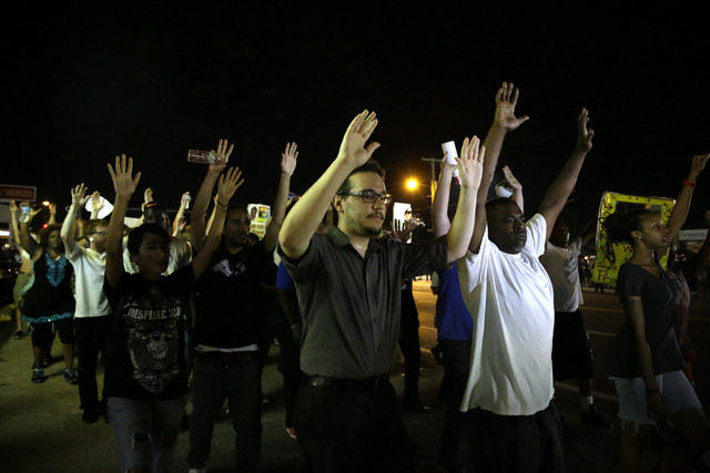 Protesters march down the street in Ferguson, Mo. Tuesday, Aug. 19, 2014. On Saturday, Aug. 9, 2014, a white police officer fatally shot Michael Brown, an unarmed black teenager, in the St. Louis  ...