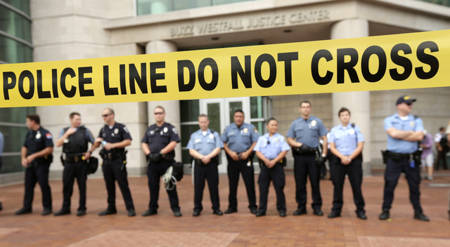Police guard the entrance to the Buzz Westfall Justice Center in Clayton, Mo., Wednesday, Aug. 20, 2014, where a grand jury is expected to convene to consider possible charges against the Ferguson ...