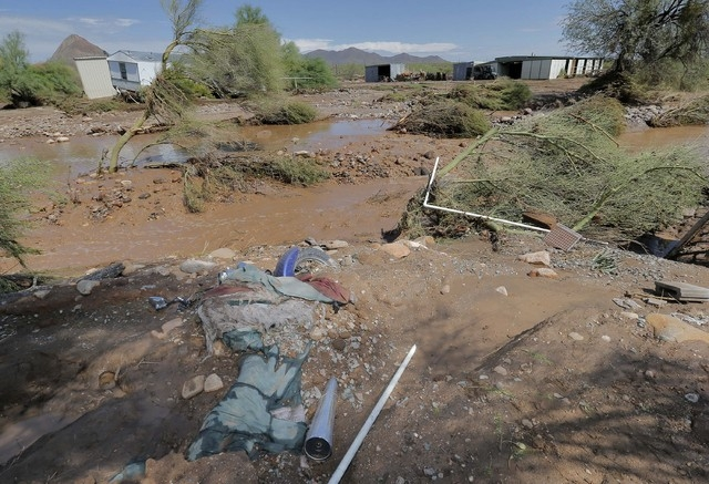 A motorcycle lies buried in mud in an area where flash flood waters  overran Skunk Creek, Tuesday, Aug. 19, 2014, in New River, Ariz., just northwest of Phoenix. (AP Photo/Matt York)