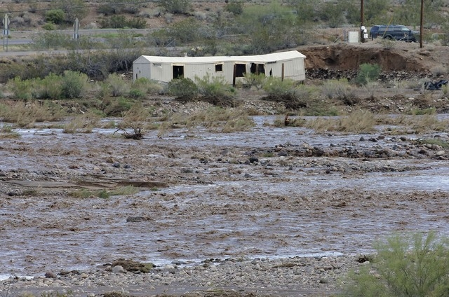 A mobile home sits ravaged in an area where flash flood waters  overran Skunk Creek, Tuesday, Aug. 19, 2014, in New River, Ariz., just northwest of Phoenix. (AP Photo/Matt York)