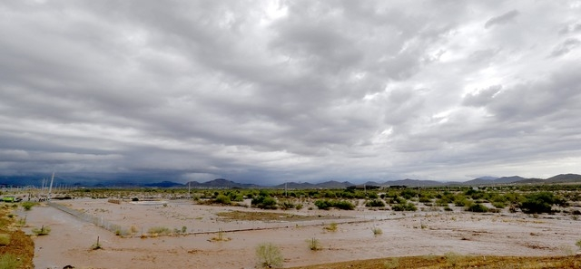 Flash flood waters overrun Skunk Creek through the Sonoran Desert, Tuesday, Aug. 19, 2014, in northwestern Phoenix. Flooding from heavy rain in the Phoenix area has forced authorities to close sev ...
