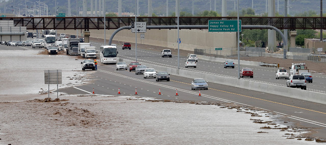 Flash flood waters from the overrun Skunk Creek flood I-10, Tuesday, Aug. 19, 2014, in northwestern Phoenix. Flooding from heavy rain in the Phoenix area has forced authorities to close several ma ...