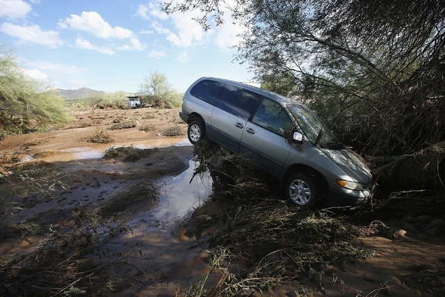 A vehicle sits atop debris where flash flood waters pushed it after rising waters overran Skunk Creek after strong storms moved through, Tuesday, Aug. 19, 2014, in New River, Ariz., just northwest ...