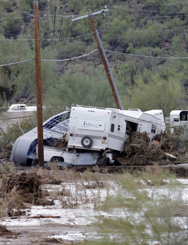 Damaged vehicles and trailers are seen in an area where flash flood waters that overran Skunk Creek, Tuesday, Aug. 19, 2014, in New River, Ariz., just northwest of Phoenix. (AP Photo/Matt York)