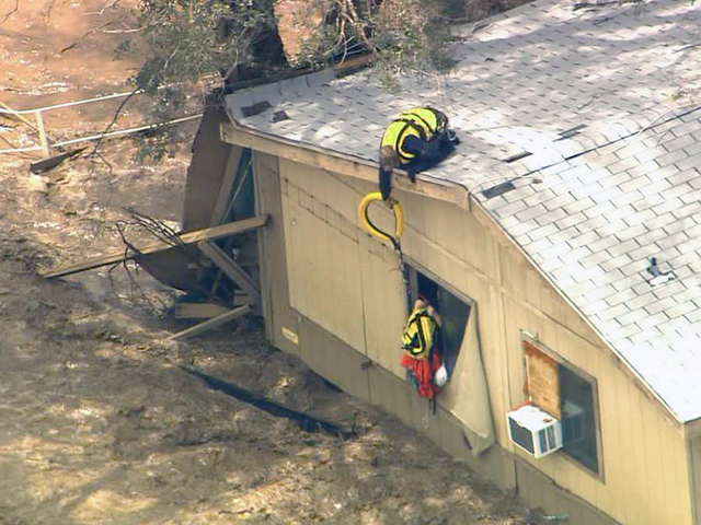 In this image made from a video provided by ABC15 TV, a rescue worker from a helicopter reaches down to residents of a flooded house in New River, Ariz., north of Phoenix, Tuesday, Aug. 19, 2014.  ...
