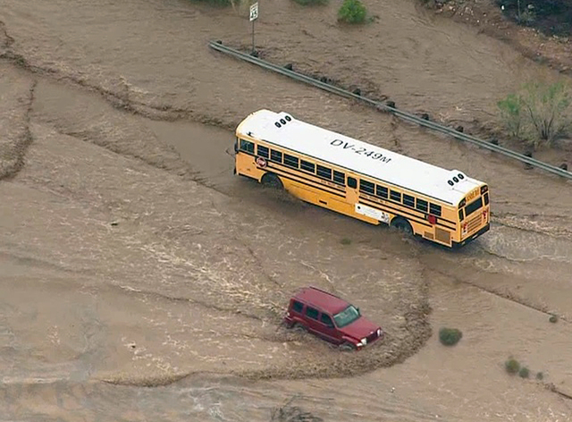 In this image made from a video provided by ABC15 TV, a school bus navigates a flooded road north of Phoenix, Tuesday, Aug. 19, 2014.  It was not known if there were children aboard the bus at the ...