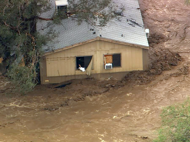 In this image made from a video provided by ABC15 TV, a man stands in the window of a flooded house in New River, Ariz., north of Phoenix, Tuesday, Aug. 19, 2014.  The area was flooded after sever ...