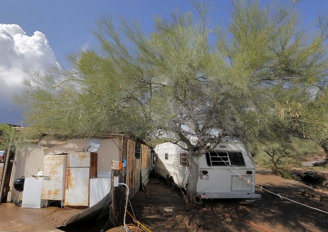 A trailer that was pushed against a tree is seen in an area of flash flood waters that overran Skunk Creek is shown, Tuesday, Aug. 19, 2014, in New River, Ariz., just northwest of Phoenix. (AP Pho ...
