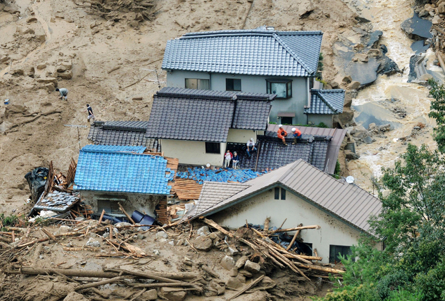 In this aerial photo, survivors and rescue workers sit on the roof of a damaged house after a massive landslide swept through residential areas in Hiroshima, western Japan, Wednesday, Aug. 20, 201 ...
