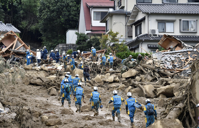 Rescue workers search for survivors after a massive landslide swept through residential areas in Hiroshima, western Japan, Wednesday, Aug. 20, 2014. Rain-sodden slopes collapsed in torrents of mud ...