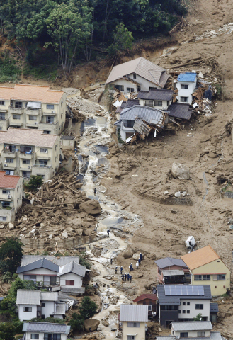 In this aerial photo, rescue workers are seen on the mud-covered ground as they search for survivors after a massive landslide swept through residential areas in Hiroshima, western Japan, Wednesda ...