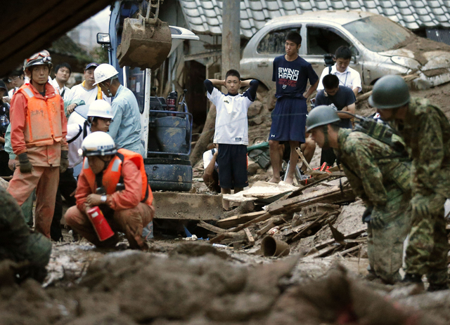 High school boys watch rescue workers search for their missing classmate after a massive landslide swept through residential areas in Hiroshima, western Japan, Wednesday, Aug. 20, 2014. Rain-sodde ...