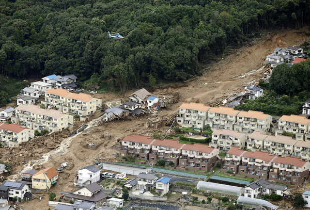 In this aerial photo, a rescue helicopter hovers  over an area devastated by a massive landslide in Hiroshima, western Japan, Wednesday, Aug. 20, 2014. A several people died and at least a dozen a ...