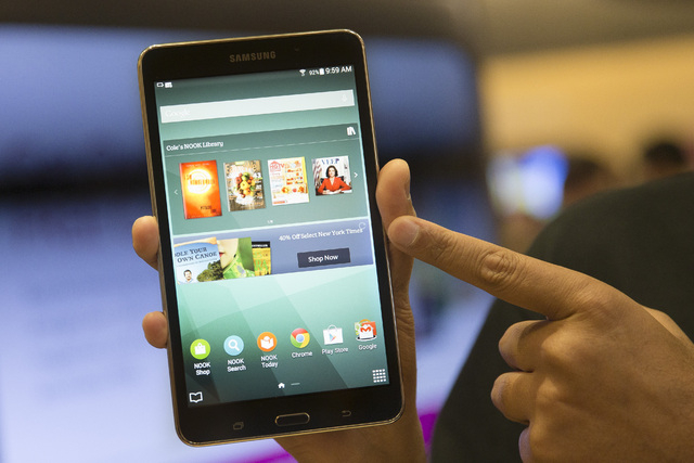 A brand ambassador handles a new Samsung Galaxy Tab 4 Nook during the unveiling of the co-branded tablet that will replace B&N's Nook, Wednesday, Aug. 20, 2014, in New York. The 7-inch tablet will ...