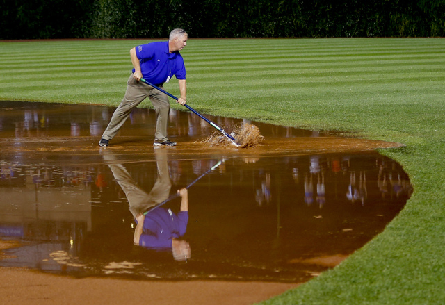 A member of the grounds crew works on the field after a heavy rain soaked Wrigley Field during the fifth inning of a baseball game between the San Francisco Giants and the Chicago Cubs on Tuesday, ...