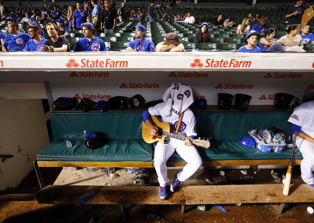 Chicago Cub backup catcher John Baker, center, plays his guitar during a rain delay at Wrigley Field during the fifth inning of a baseball game between the San Francisco Giants and the Chicago Cub ...