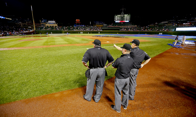 The umpires look over the field after a heavy rain soaked Wrigley Field during a baseball game between the San Francisco Giants and the Chicago Cubs in the fifth inning Tuesday, Aug. 19, 2014, in  ...