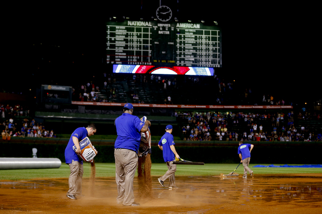 The grounds crew works on the field after a heavy rain soaked Wrigley Field during the fifth inning of a baseball game between the San Francisco Giants and the Chicago Cubs on Tuesday, Aug. 19, 20 ...