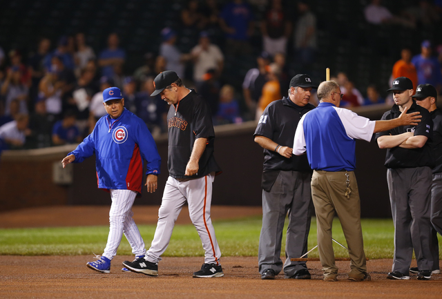 Chicago Cubs manager Rick Renteria and San Francisco Giants manager Bruce Bochy talk with the umpires and officials on the field after a heavy rain soaked Wrigley Field during the fifth inning of  ...