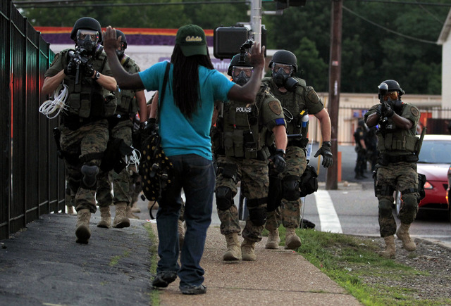 FILE - In this Aug. 11, 2014 file photo, police wearing riot gear walk toward a man with his hands raised in Ferguson, Mo. The response to Browns death turned violent because of a convergence of f ...