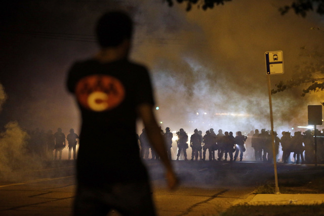FILE - In this Aug. 13, 2014 file photo, a man watches as police walk through a cloud of smoke during a clash with protesters in Ferguson, Mo. The response to Browns death turned violent because o ...