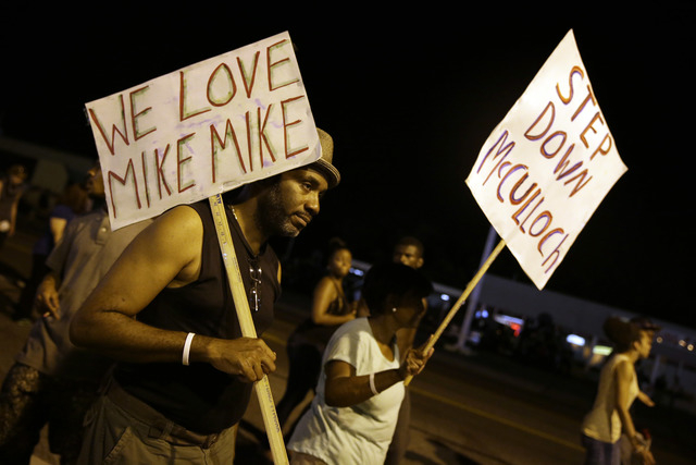 Protesters march Thursday, Aug. 21, 2014, in Ferguson, Mo. Protesters again gathered Thursday evening, walking in laps near the spot where Michael Brown was shot. Some were in organized groups, su ...