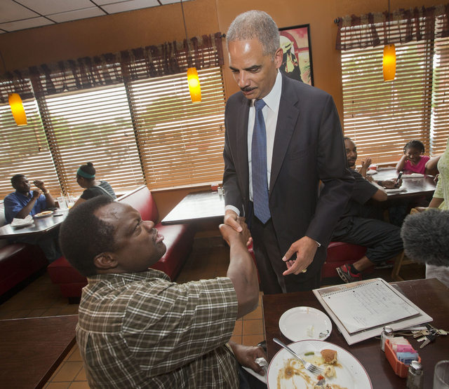 Attorney General Eric Holder stops to shake hands with a patron at Drake's Place Restaurant, before his meeting with local community leaders, Wednesday, Aug. 20, 2014 in Ferguson, Mo. Holder arriv ...