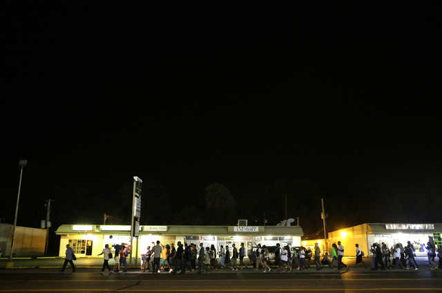 A line of protesters march into the evening Thursday, Aug. 21, 2014, in Ferguson, Mo. Protesters again gathered Thursday evening, walking in laps near the spot where Michael Brown was shot. Some w ...