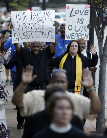 Protesters march to the Buzz Westfall Justice Center Wednesday, Aug. 20, 2014, in Clayton, Mo. A grand jury has begun hearing evidence as it weighs possible charges against the Ferguson police off ...