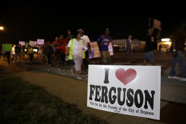 Protesters march Thursday, Aug. 21, 2014, in Ferguson, Mo. Protesters walked in laps near the spot where Michael Brown was shot. Some were in organized groups, such as clergy members. More signs r ...