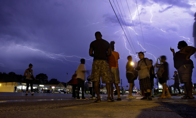 Protesters stand in the street as lightning flashes in the night sky in Ferguson, Mo. on Wednesday, Aug. 20, 2014. A grand jury has begun hearing evidence as it weighs possible charges against the ...
