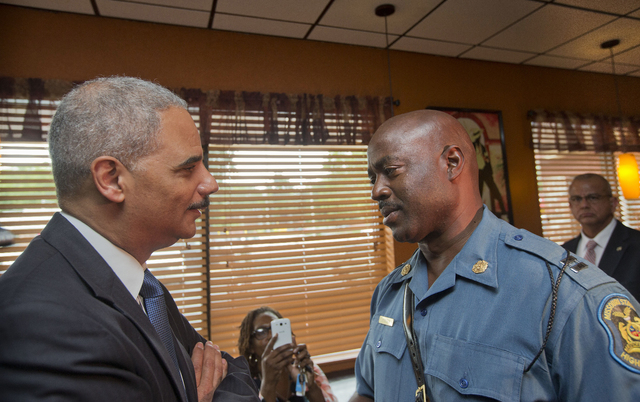 Attorney General Eric Holder speaks with Capt. Ron Johnson of the Missouri State Highway Patrol at Drake's Place Restaurant, Wednesday, Aug. 20, 2014, in Ferguson, Mo. Holder arrived in Missouri o ...
