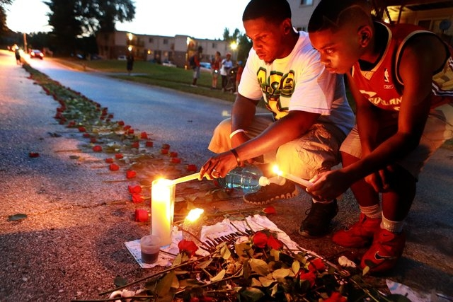 Theo Murphy, left, of Florissant, Mo., and his brother Jordan Marshall, 11, light candles at a memorial on Canfield Drive in Ferguson, Mo., Thursday, Aug. 21, 2014, where where unarmed Michael Bro ...